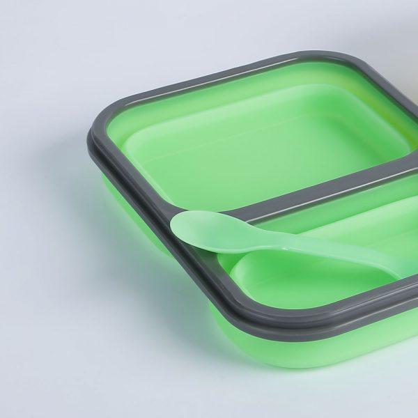 Detalle fiambrera plegable de silicona con dos recipientes y cubierto destapada con cubierto.
