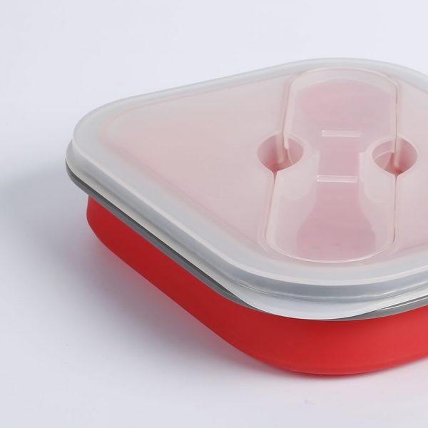 Detalle lateral de la fiambrera plegable de silicona con un recipiente y cubierto.